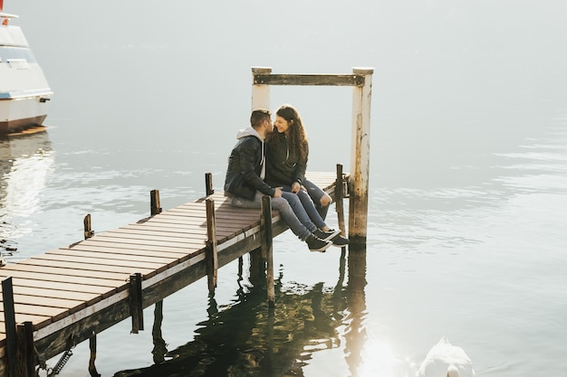 スイスのルガーノ湖にある木製の桟橋にいる魅力的なカップル。 Premium写真