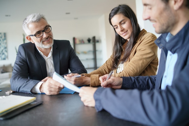 Attractive couple signing contract with real-estate agent in contemporary house Premium Photo
