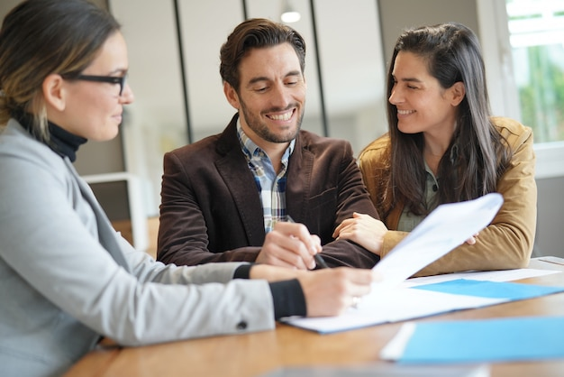 Attractive couple signing sales agreement with real estate agent Premium Photo