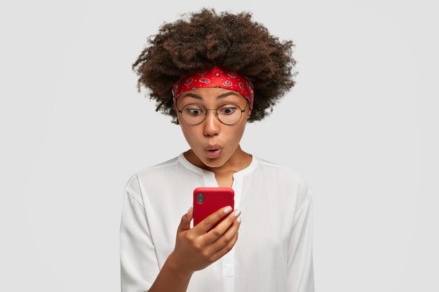 Симпатичная кудрявая темнокожая женщина с афро-прической взволнованно смотрит на экран смартфона, впечатлена сообщением, полученным от друга, удивлена выражением лица, стоит в помещении Бесплатные Фотографии