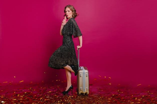 포장 된 가방이 한쪽 다리에 서있는 매력적인 곱슬 여성 모델 무료 사진
