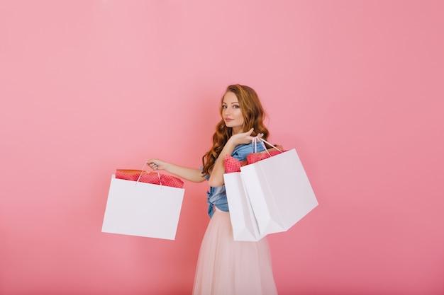 분홍색 배경에 고립 된 의류 매장에서 큰 흰색 가방을 들고 데님 셔츠에 매력적인 곱슬 소녀. 쇼핑 후 패키지와 함께 포즈를 취하는 귀여운 옷에 매력적인 긴 머리 젊은 여자. 무료 사진