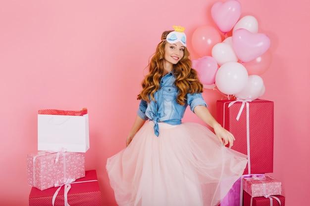 유행 무성한 치마에 매력적인 곱슬 소녀는 배경에 선물과 함께 생일 파티에 손님을 기다리고 있습니다. 사랑스러운 젊은 여성이 친구로부터받은 풍선과 선물을 즐깁니다. 무료 사진