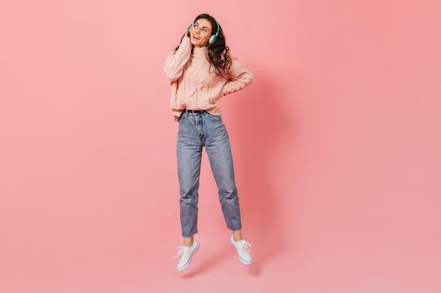 Attraente donna riccia in jeans e maglione blu mamme saltando su sfondo rosa, ascoltando la canzone in cuffia. Foto Gratuite