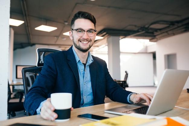 魅力的な黒髪の男は、オフィスのテーブルで働いています。彼は黒いジャケットの青いシャツを着ています。彼は一杯のコーヒーを飲みながらカメラに微笑んでいます。 無料写真