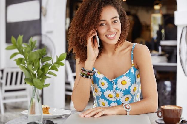 魅力的な黒肌の女性は、屋外カフェで電話で会話し、おいしいケーキとカプチーノを楽しんでおり、友人と最新のニュースを共有しています。 無料写真