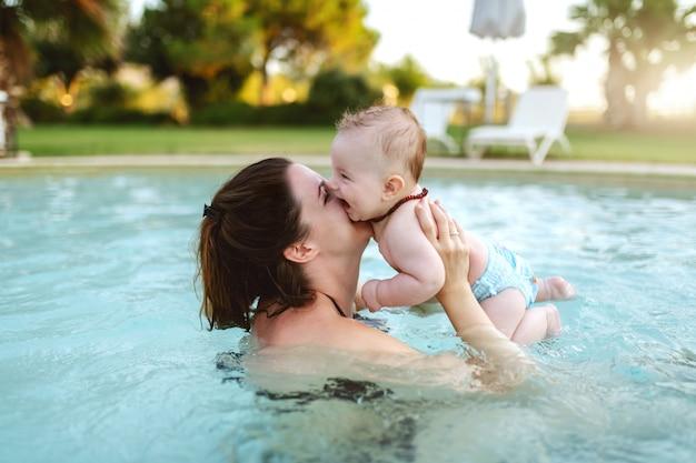 魅力的な献身的な白人ブルネットは、スイミングプールに立っている間彼女の愛情のある6ヶ月の息子にキスします。プールのコンセプトで初めて。 Premium写真