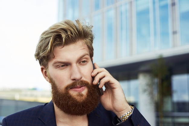 魅力的な疑わしい男が携帯電話で話し、ビジネスビルの近くで屋外を歩きます。スーツを着た真面目な人。 無料写真