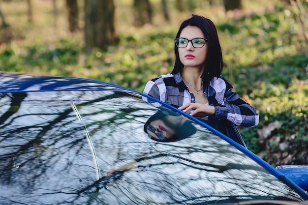Attractive driver girl looks out of open door of car Premium Photo