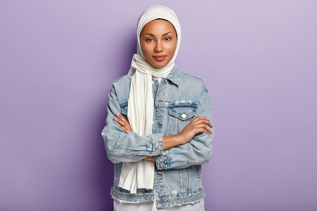 Attractive eastern woman covers head with white headscarf to guard her dignity and power, has special dress code, keeps hands crossed, looks with modesty, poses over purple wall. islamic rules Free Photo