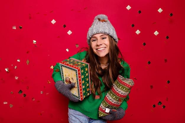 Привлекательная энергичная молодая леди в зимнем наряде держит праздничные подарки на изолированном красном фоне с конфетти, празднование, новый год, день рождения, счастливое настроение Бесплатные Фотографии