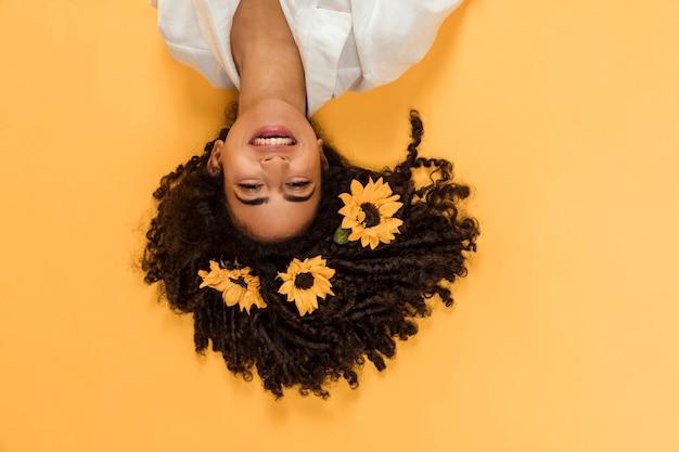 머리에 꽃을 가진 매력적인 민족 웃는 여자 프리미엄 사진