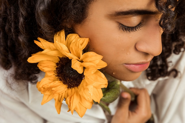 Attractive ethnic weeping woman with flower Free Photo