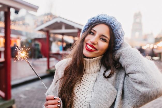 ベンガルの光を保持している通りで新年を祝う灰色のコートを着た魅力的なヨーロッパの女性。冬の線香花火でポーズをとって赤い唇と幸せなブルネットの少女の屋外のポートレート。 無料写真