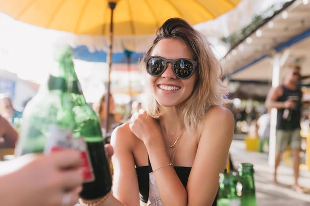 카페에서 맥주를 마시고 웃고 매력적인 국방과 소녀. 여름 날에 야외 레스토랑에서 친구와 함께 시간을 보내는 젊은 여자를 흥분. 무료 사진