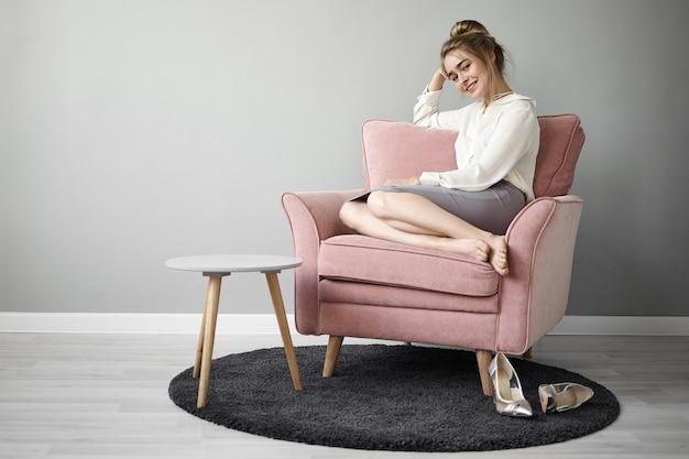 Attraente giovane donna europea alla moda con chignon e piedi nudi comodamente seduti in poltrona rosata e sorridente, godendosi il tempo libero da sola, eleganti scarpe col tacco alto sul tappeto Foto Gratuite