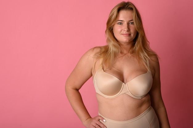 Attractive fat woman with measuring tape on pink wall Premium Photo