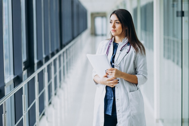 Attractive female doctor standing with documents at the hospital Free Photo