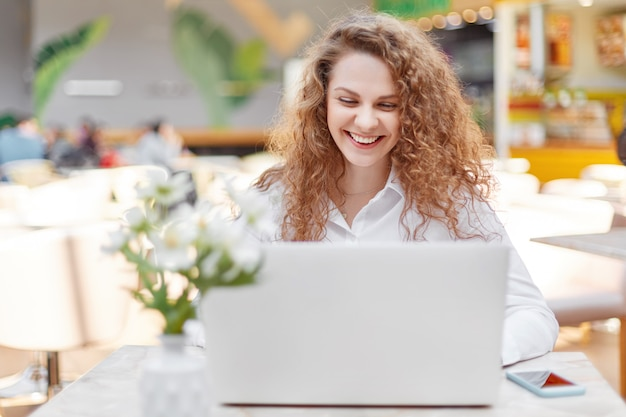Attractive female freelancer works remotely on portable laptop computer Free Photo