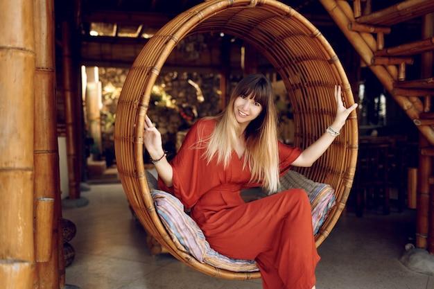 Ubicazione femminile attraente nell'attaccatura della scala di bambù sulla veranda all'aperto del bungalow di legno Foto Gratuite