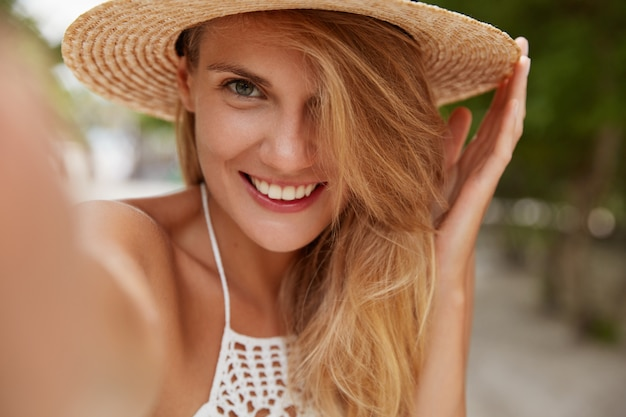 Donna attraente con un sorriso piacevole, capelli chiari, indossa un cappello estivo, fa selfie con un dispositivo irriconoscibile mentre cammina all'aperto, gode di splendidi paesaggi e di un clima caldo e splendente. felice donna Foto Gratuite