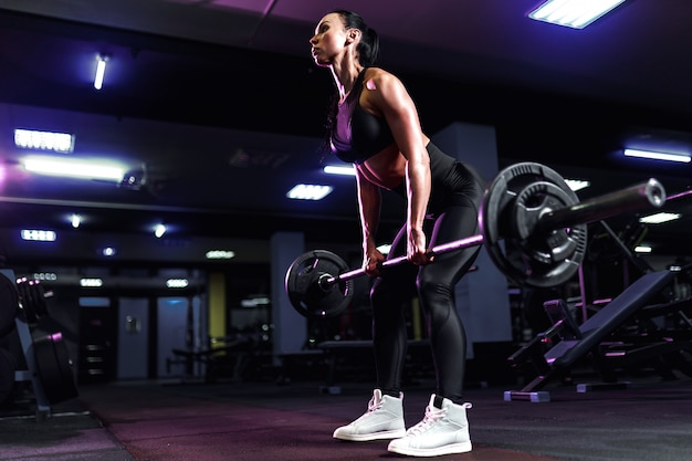 Attractive fit sexy woman in the gym crouches with a barbell. woman training back Premium Photo
