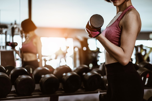 Attractive fit woman workout with dumbbell in gym fitness Premium Photo