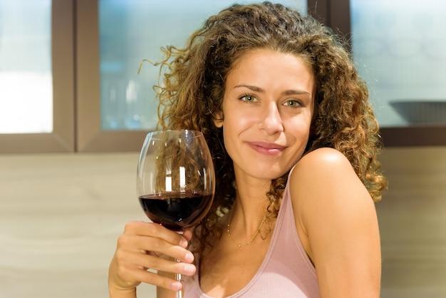 Привлекательная дружелюбная молодая женщина с прекрасной теплой улыбкой тостов с большим элегантным бокалом красного вина, чтобы отпраздновать это крупным планом Premium Фотографии