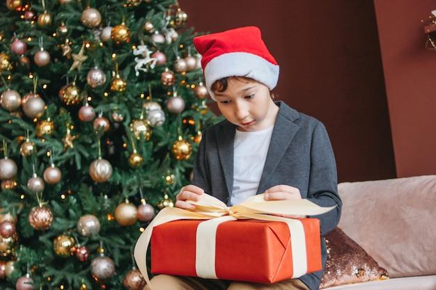 Attractive funny tween boy with dark hair in santa hat open gift box on christmas tree Premium Photo