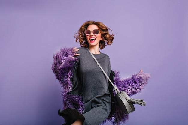 회색 드레스와 보라색 배경에 스튜디오에서 춤을 검은 선글라스에 매력적인 여자 무료 사진