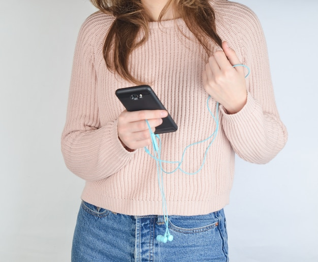 청바지와 스웨터에 매력적인 여자는 스마트 폰 및 헤드폰을 들고있다. 프리미엄 사진