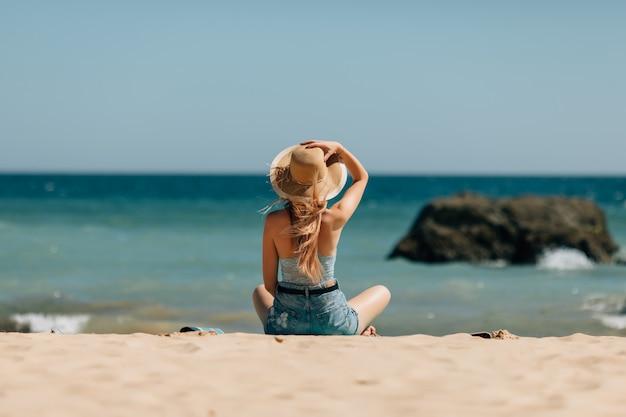 暖かい砂の上にあるサングラスと帽子で魅力的な女の子 無料写真