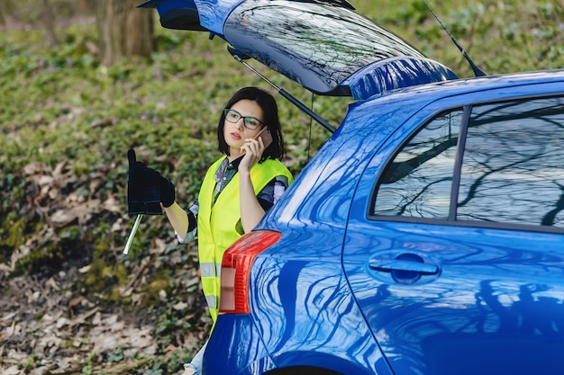 Attractive girl talking by phone near car on road in safety jacket Premium Photo