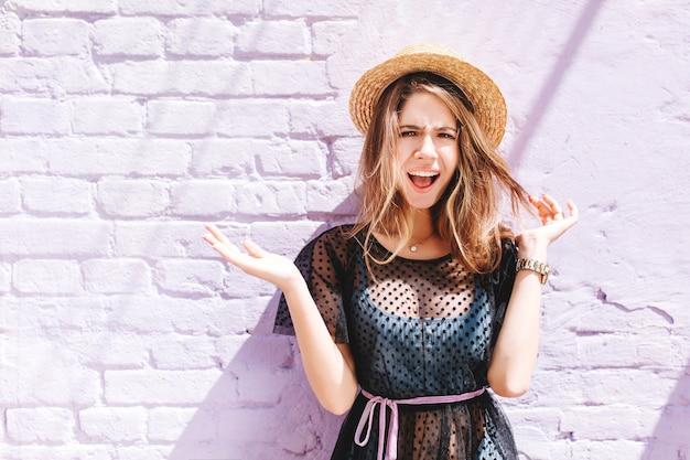 Attraente ragazza indossa cappello estivo e orologio da polso in posa con i palmi rivolti verso l'alto e l'espressione del viso incredulo Foto Gratuite