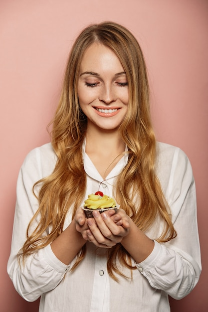 Attractive girl in a white shirt is holding cupcakes Free Photo