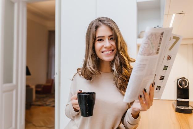 雑誌を保持し、彼女の部屋で笑っている薄茶色の髪の魅力的な女の子 無料写真