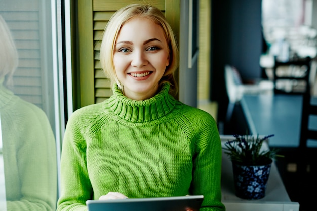 Attractive girl with light hair wearing green sweater sitting in cafe with tablet, freelance concept, online shopping, portrait. Premium Photo