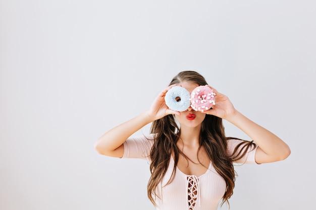 Ragazza attraente con capelli lunghi del brunette che tiene le ciambelle colorate contro i suoi occhi. gioiosa giovane donna con labbra rosse divertendosi con i dolci, deliziosi. vita brillante. espressioni, concetto di dieta. Foto Gratuite