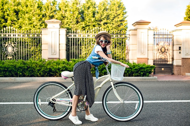 Attractive girl with long curly hair in hat posing with bike on road. she wears long skirt, jerkin, blue sunglasses. she is smiling to camera. Free Photo