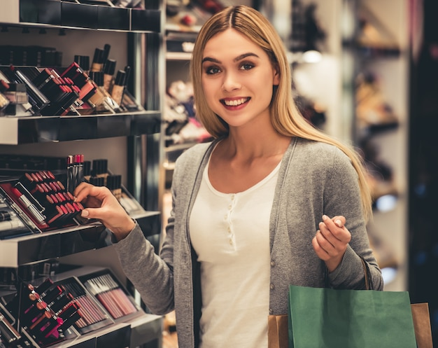 Attractive girl with shopping bags is choosing lipstick Premium Photo