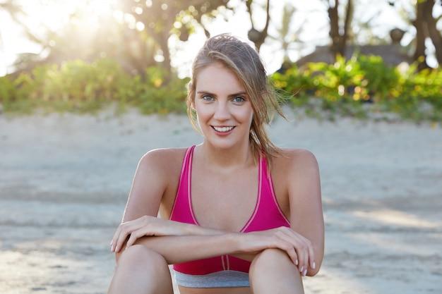 魅力的なうれしそうな女性のジョガーはやる気があり、砂浜で朝のトレーニングをしていて、一人で休んでいて、ピンクのトップを着ています。アクティブなライフスタイルに関わるスポーツウーマン。人、フィットネス、屋外エクササイズ 無料写真
