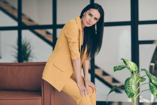 Привлекательная гламурная дама позирует возле дивана Premium Фотографии
