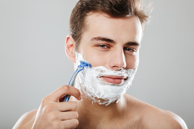 Attractive guy with dark short hair shaving his face with razor and gel or cream being isolated  over grey wall close up Free Photo
