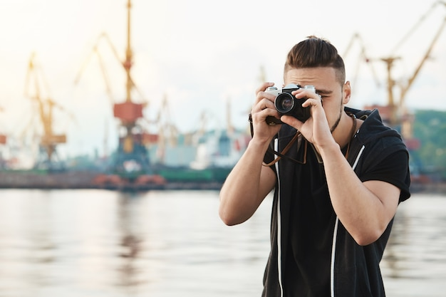 Attractive guy working with camera. young stylish photographer looking through camera during photo session with gorgeous model, taking pictures in harbour near seashore, focusing on work Free Photo