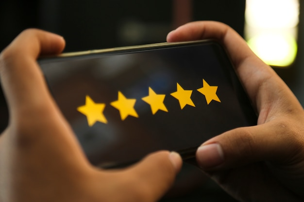 Attractive hands giving five stars rating on a smart phone Premium Photo