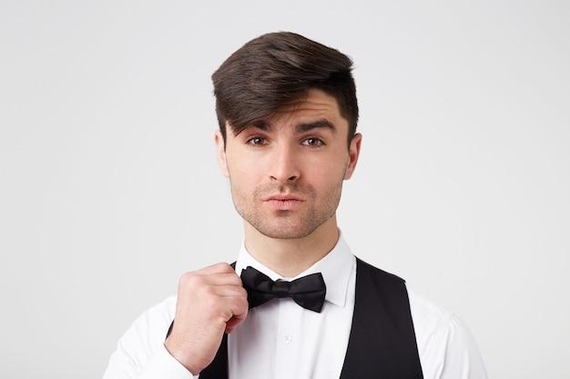 Attraente bel ragazzo dai capelli scuri elegantemente vestito corregge il suo farfallino, sembra affascinante Foto Gratuite