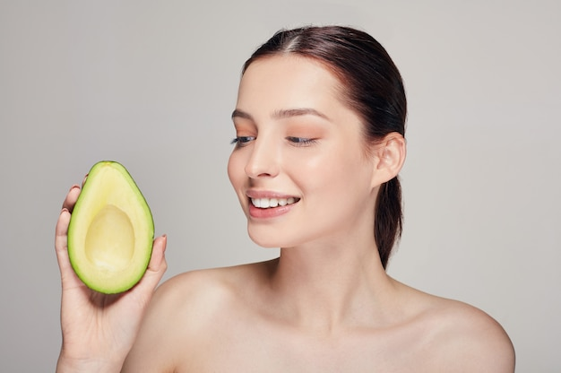 Attractive happy and cheerful lady with pure shine skin with avocado Premium Photo