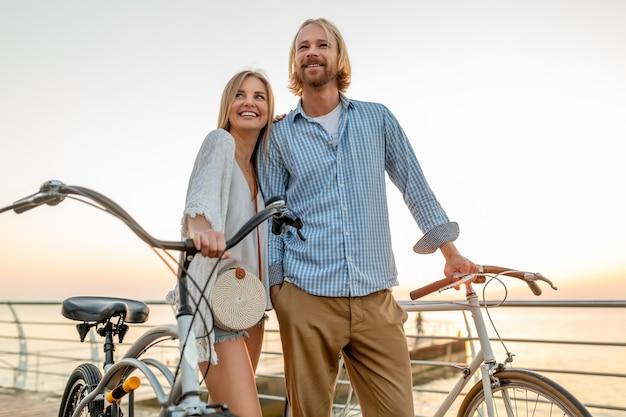 Привлекательная счастливая пара друзей, путешествующих летом на велосипедах, мужчина и женщина со светлыми волосами в стиле хипстера в стиле бохо, весело проводящие время вместе, гуляя по берегу моря в курортном городе Бесплатные Фотографии
