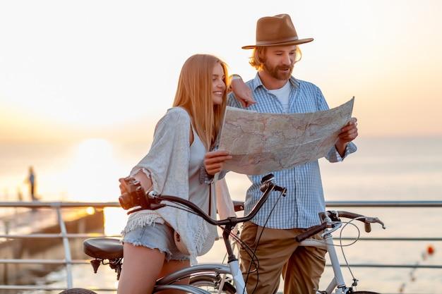 Привлекательная счастливая пара, путешествующая летом на велосипедах, мужчина и женщина со светлыми волосами в стиле хипстера в стиле бохо, весело проводящие время вместе, глядя на карту достопримечательностей Бесплатные Фотографии