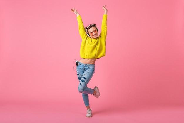 Привлекательная счастливая смешная женщина в желтом свитере танцует, слушая музыку в наушниках, одетая в красочный хипстерский наряд, изолированный на розовой стене, весело Бесплатные Фотографии